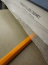 Using wax paper to protect the book, smush the glued pages in the book to solidify the spine.